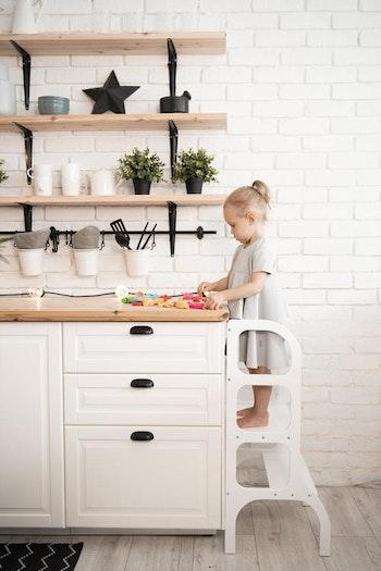 Liten tjej som leker med pedagogiska leksaker i en learning tower från Only Handmade