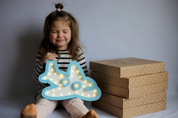 Ett barn som håller nattlampan i trä från Only Handmade