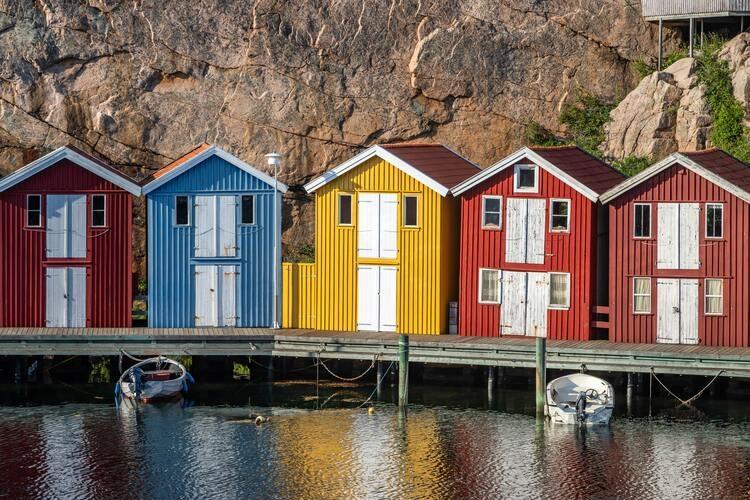 Färgglada sjöbodar på en brygga vid havet illustrerar strandskyddsdispens för sjöbod.