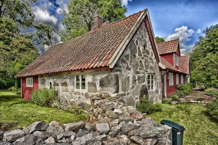 En gammal byggnad i sten illustrerar strandskyddsdispens för ändrad användning.
