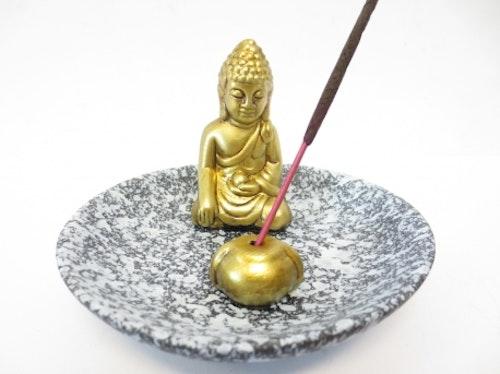 Gyllene Buddha sittandes på grått fat Rökelsehållare