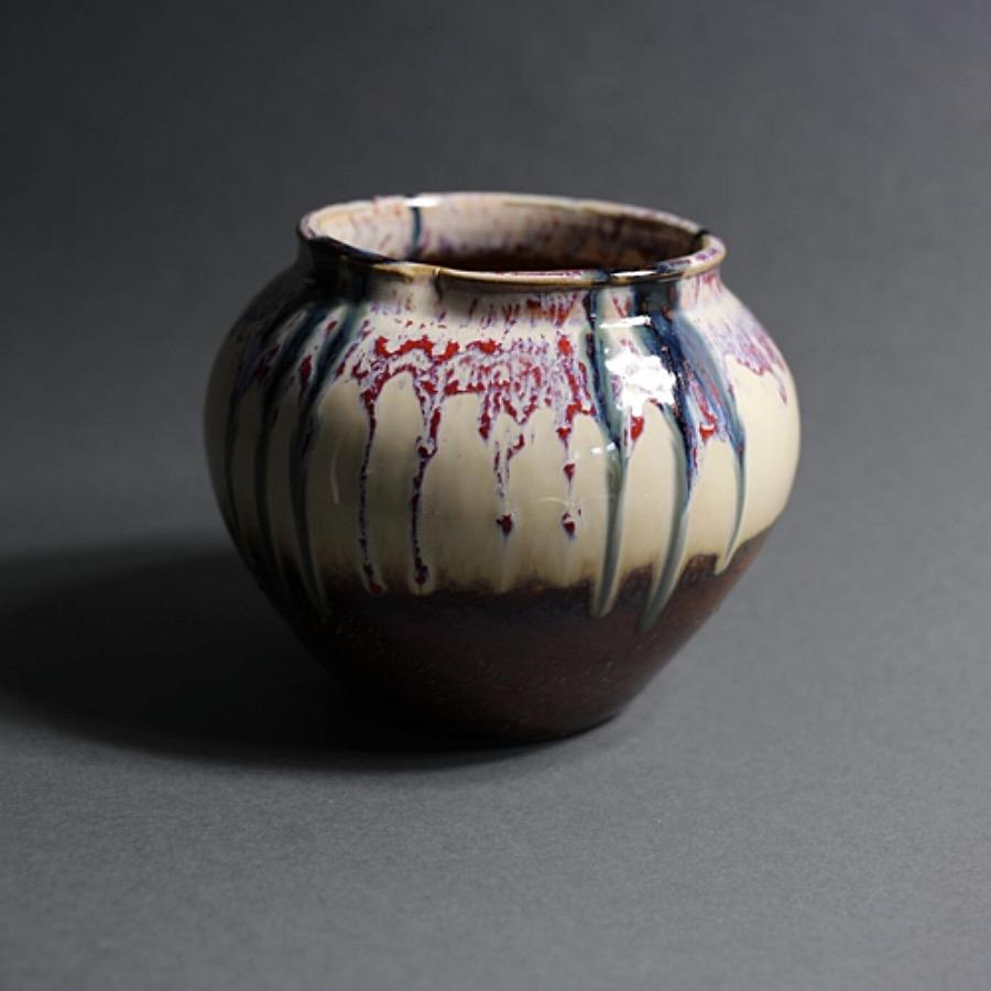 Melting flower vase är en keramikkruka i unik design med oregelbunden form. Glaseringstekniken går från färgerna sierra till cremefärgatt med oxblodsröda fläckar. 18 x 19 cm The Arni Concept