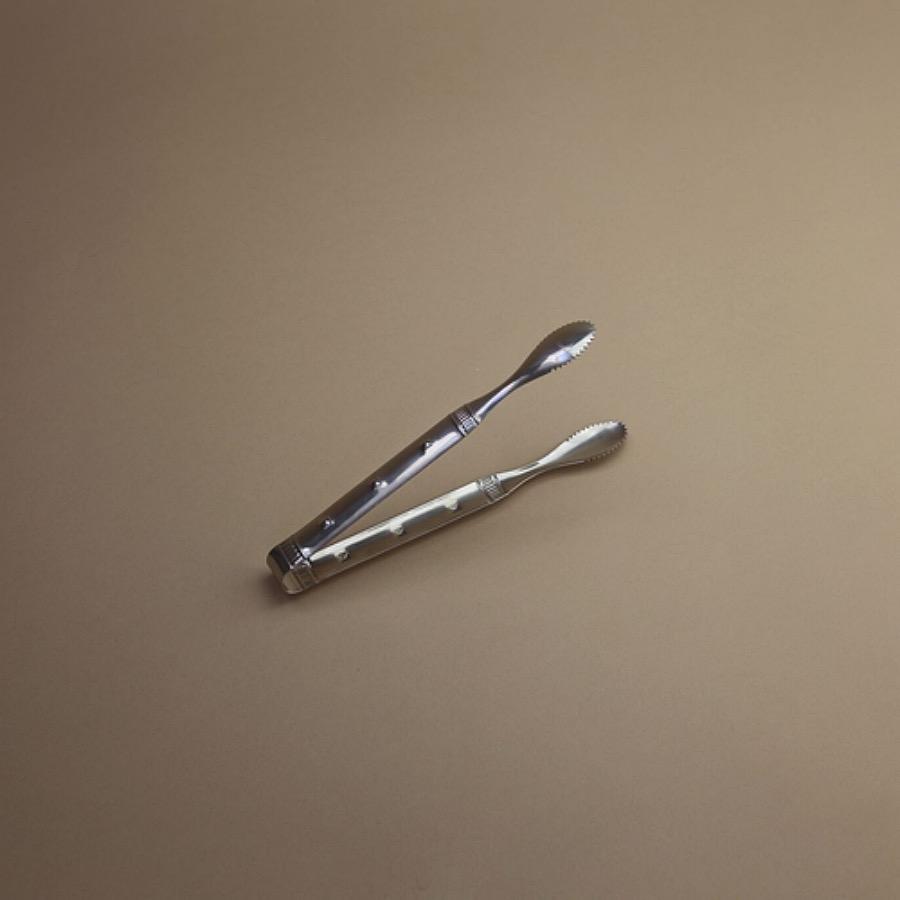 Serving tong - large är en serveringstång i rustik rostfritt stål. Mått: Längd 12 cm, Bredd 2 cm. The Arni Concept.