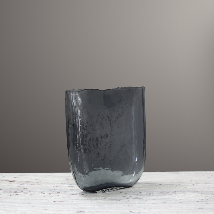 Mia Vas Grå. Vasen är gjord utav ett grått rökigt glas och den abstrakta formen speglar ljuset på ett vackert sätt. Olsson & Jensen  Art.Nr: DS011621, Mått  H 25 cm  B 24 cm. The Arni Concept