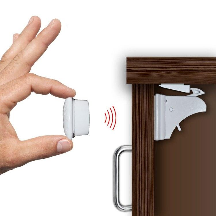 Hand som låser upp ett osynligt barnlås med en magnet-nyckel
