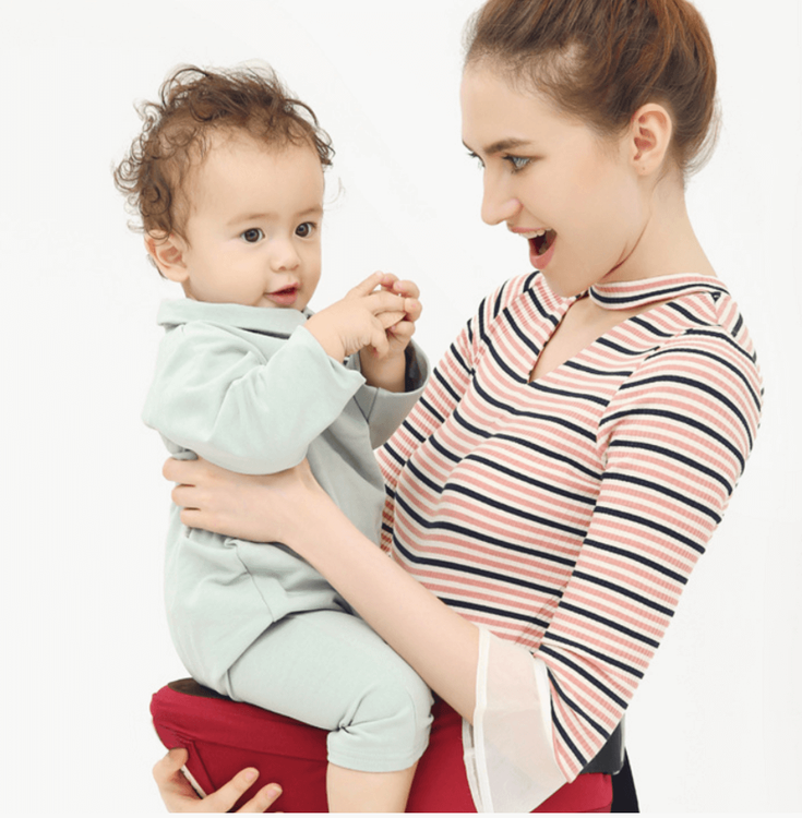 Kvinna bär sitt barn med sin höftsele