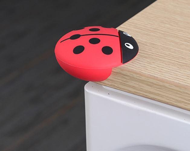 Hörnskydd som ser ut som en röd nyckelpiga, monterat på ett bordshörn