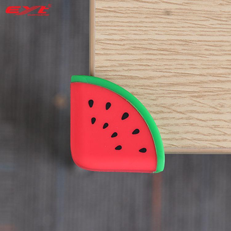 Hörnskydd som ser ut som en röd vatten melon, monterat på ett bordshörn