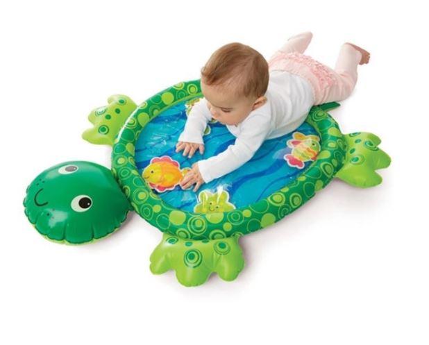 Baby som leker med lekmatta till baby som ser ut som en sköldpadda