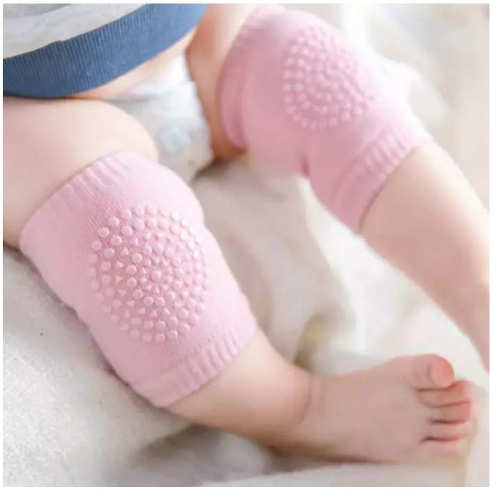 Bebis som har rosa knäskydd på sif