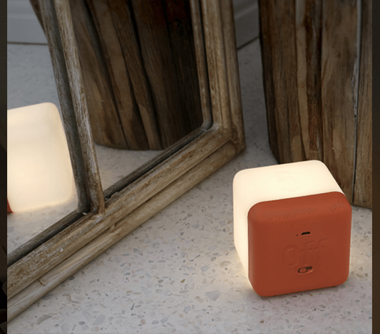 Fin nattlampa form av en vit kub med orange botten som lyser upp ett rum
