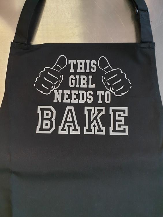 """Förkläde med tryck """"This Girl Needs To Bake"""" FYNDHÖRNA"""