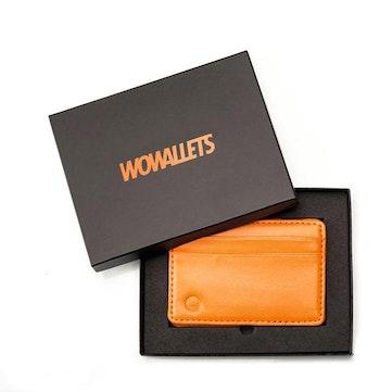 Orange läderplånbok i presentask där locket är öppnat men ligger över ett hörn av plånboken