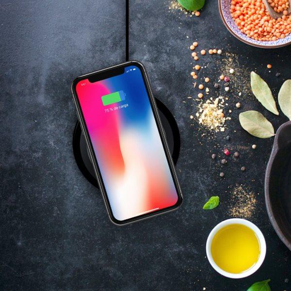 Minibatt UltraSLIM trådlös laddare laddar iPhone på svart bord