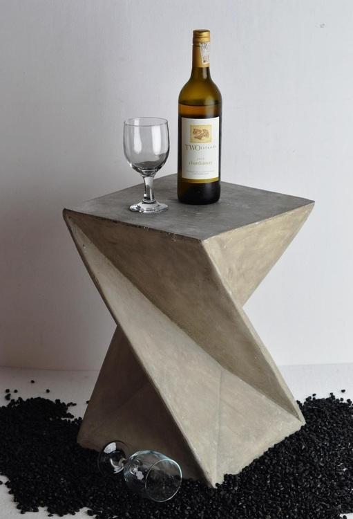 Sidobord av betong med vinflaska och vinglas på