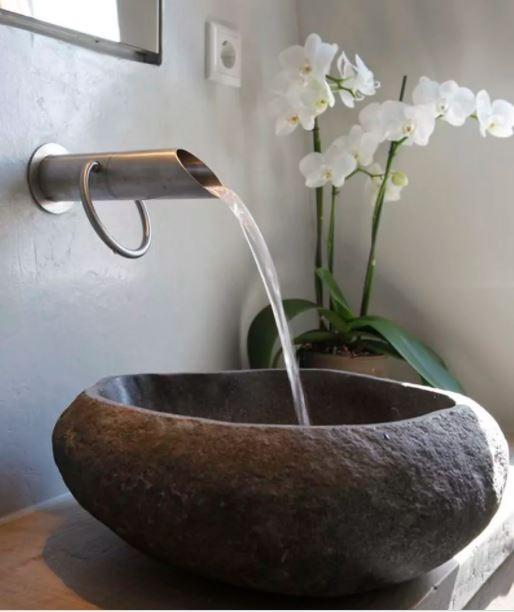 Kran som spolar vatten i handfat av sten