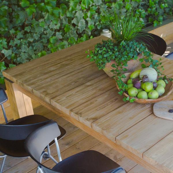 Matbord av teak med skålar på och stolar bredvid