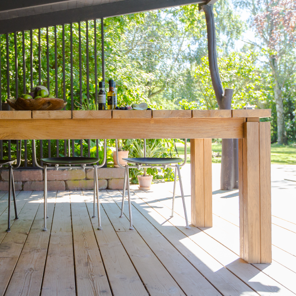 Matbord av teak som står på trädäck