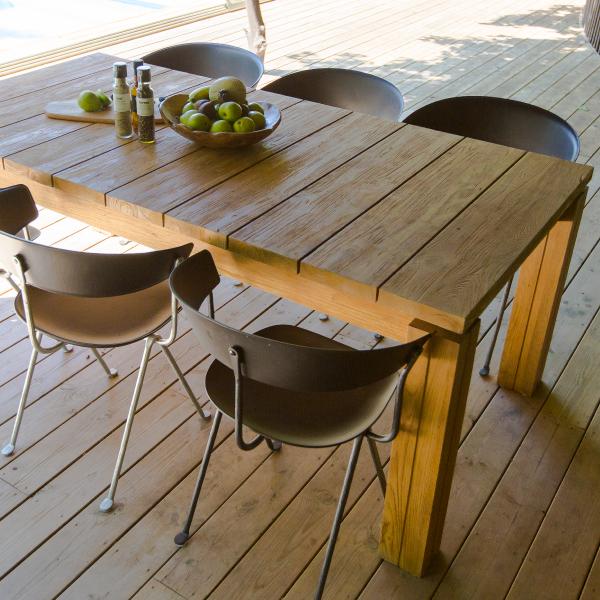 Matbord av teak med stolar på trädäck