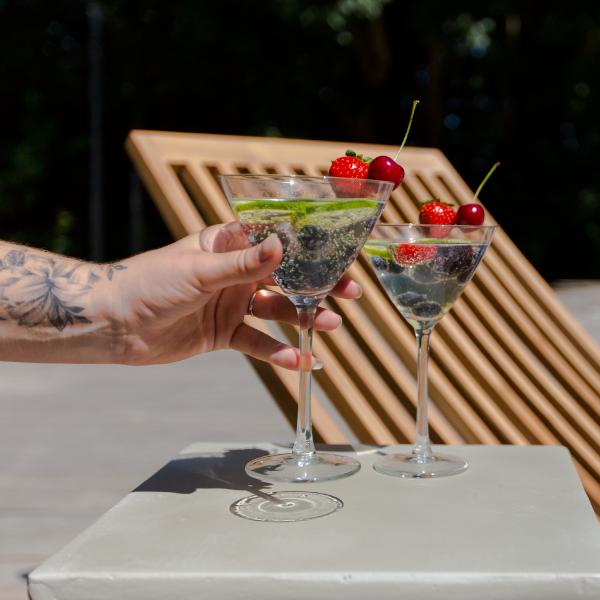 Solstol av teak med två cocktailglas