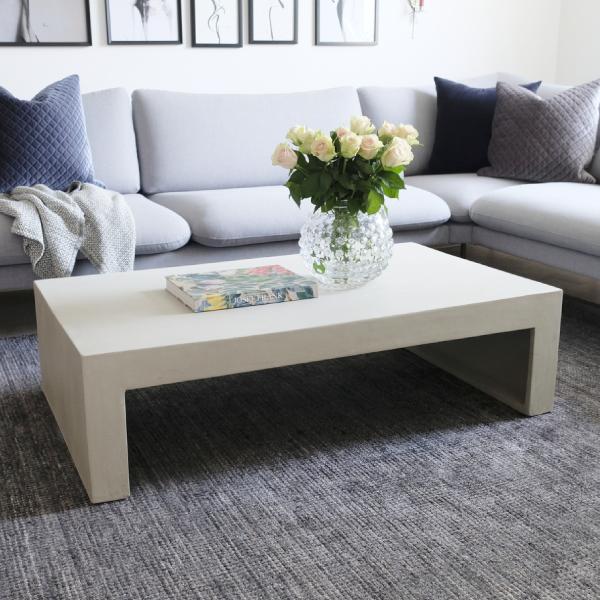Soffbord av betong vid grå soffa