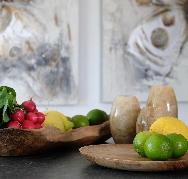 Ljushållare av onyx på bord med skål och fat med frukt och grönt
