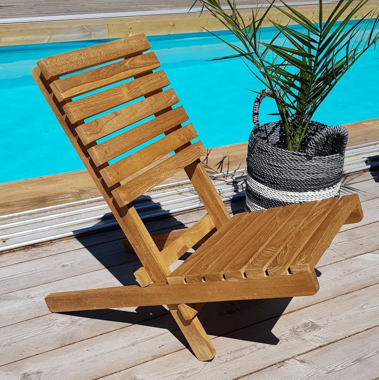 Strandstol av trä på trädäck bredvid pool