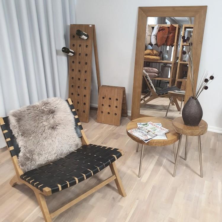 interiör med träfåtölj, bord och stor spegel