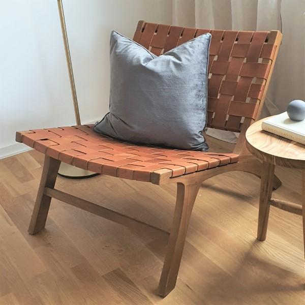 träfåtölj med lädersits och blå kudde