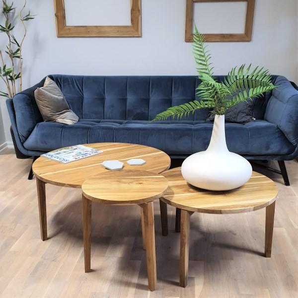 Tre soffbord av trä framför blå soffa
