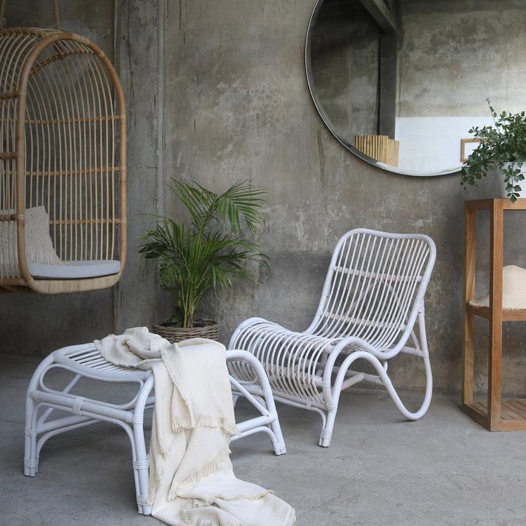 Rottingstol och rottingpall med pläd i ett rum
