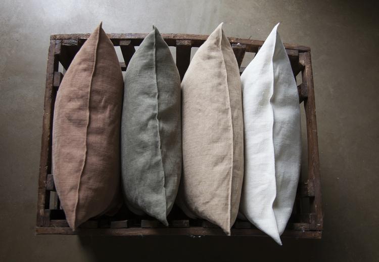 I en trälåda ligger linnekuddar. De har bleka linnefärger: Ljungröd, olivgrön, beige och vit.