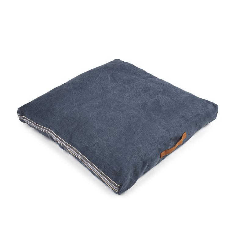 Denimblå, fyrkantig golvkudde med läderhandtag på sidan.