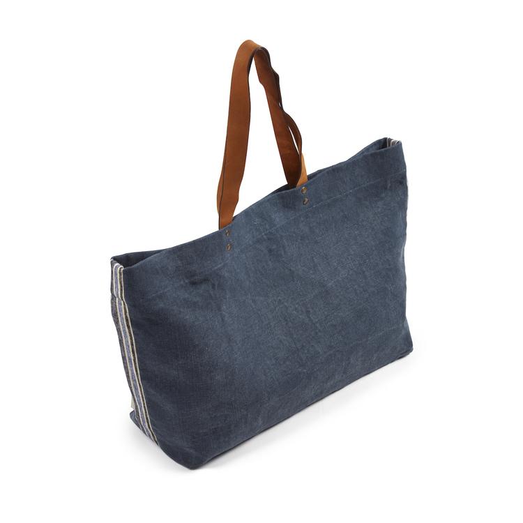 Denimblå axelväska med bruna läderhandtag.