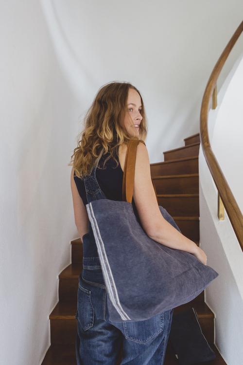 Kvinna med väskan över axeln. Väskans närliggande sida har randigt kantband.