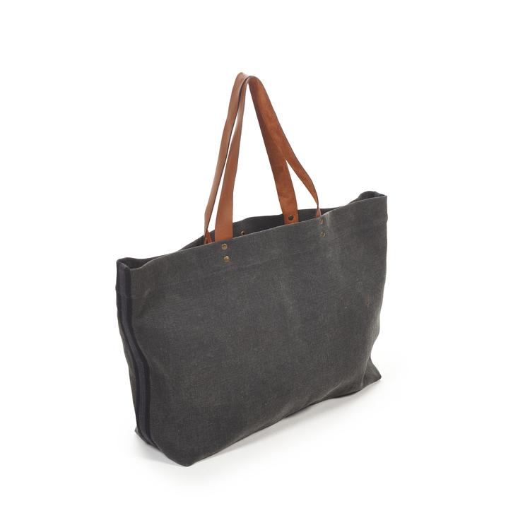Blekt svart axelväska med bruna läderhandtag.