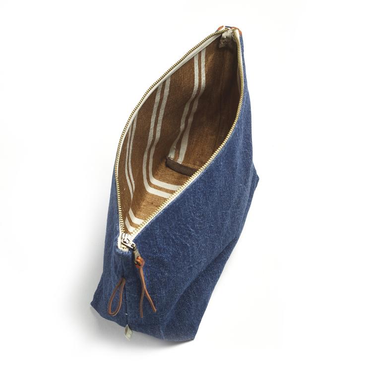 Necessär i blå denim med kantrand i brons, benvitt och marinblått och foder med rand i vitt och brons. Blixtlås i guldmetall, ögla och dragstropp i läder.