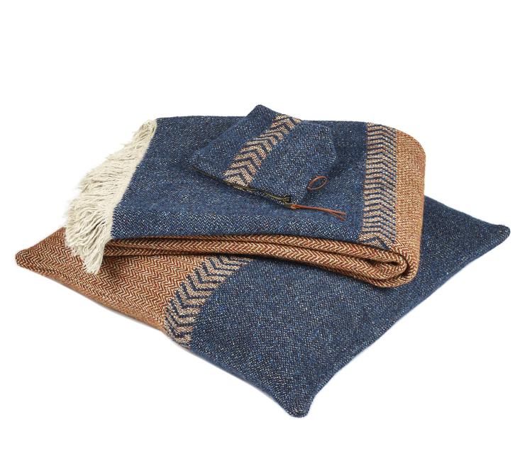 Mini-necessären ligger ovanpå matchande mörkblå och rostfärgad kudde och pläd.