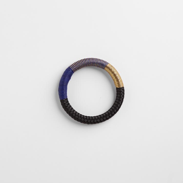 Armband av svart rep. Partier av repet är virat med guldlurex och blå bomullstråd.
