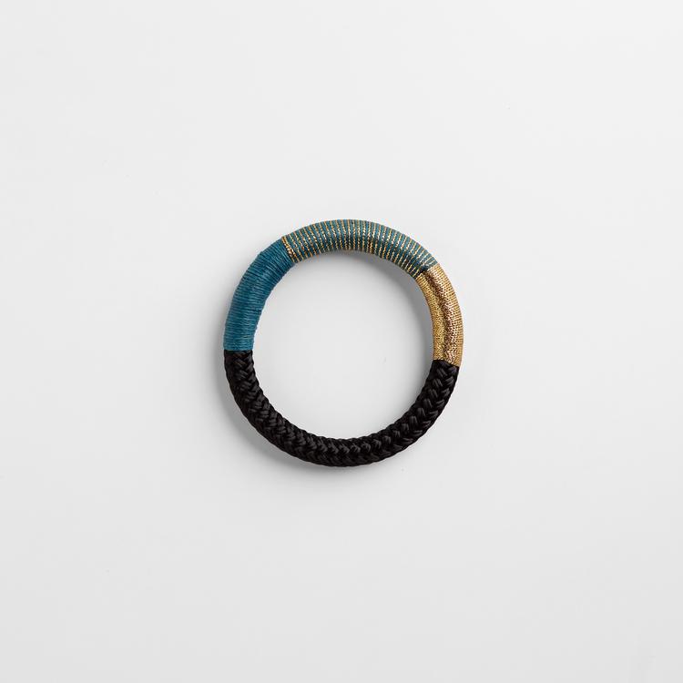 Armband av svart rep. Partier av repet är virat med guldlurex och turkos bomullstråd.