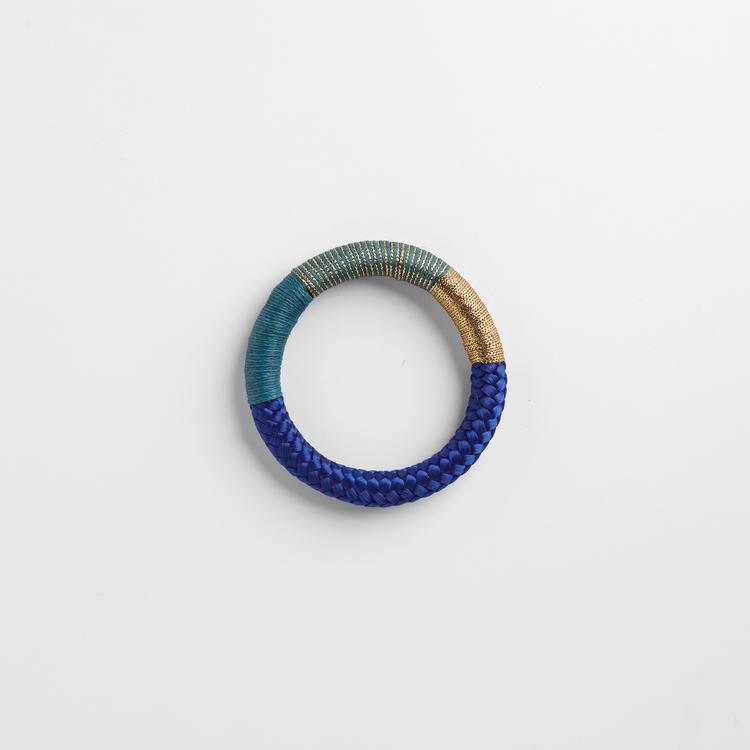 Armband av blått rep. Partier av repet är virat med guldlurex och turkos bomullstråd.