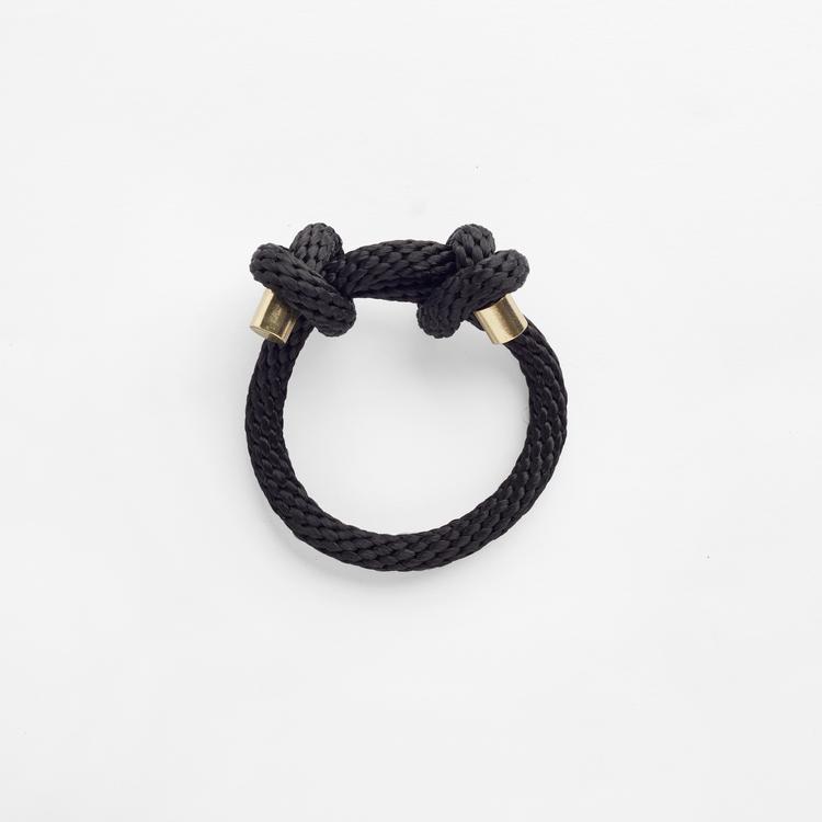 Armbandet är flätat i mjukt svart rep som går omlott. Justerbart via konstfärdiga knutar, med guldhylsor i ändarna.