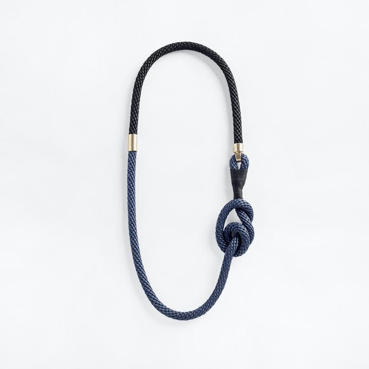 Halsband av svart och blått rep med en stor knut och ögla omlindad av svart vaxad bomullstråd. Symmetriska guldmetall-hakar på var sida.