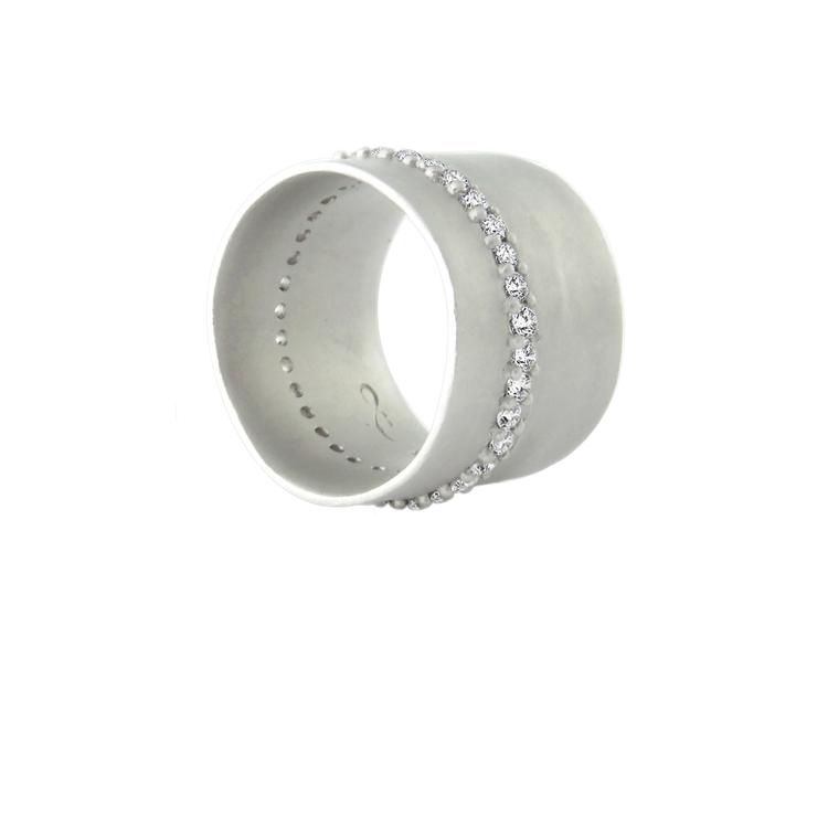 Själva bandet har en underbar matt yta som blir alldeles perfekt till ringens gnistrande band av vita safirer. Lotta Jewellery har skapat en magnifik ring som aldrig slutar glittra!