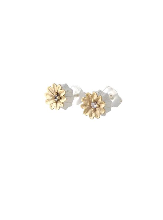 Poppy Stud Earrings från Lotta Jewellery är tillverkade i frostat silver och dekorerade med 14 k matt guld och glittrande vita safirer.