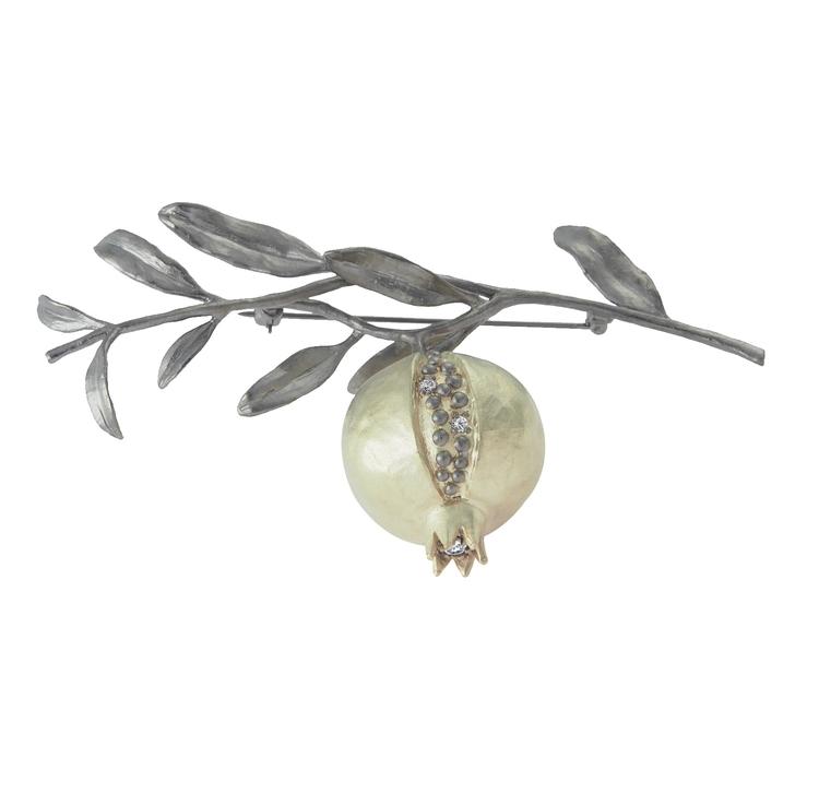 Broschen är gjord i matt brons med detaljer i 14 k guld. Vita safirer pryder broschen fram till och i fruktens krona sitter ännu en glittrande safir.