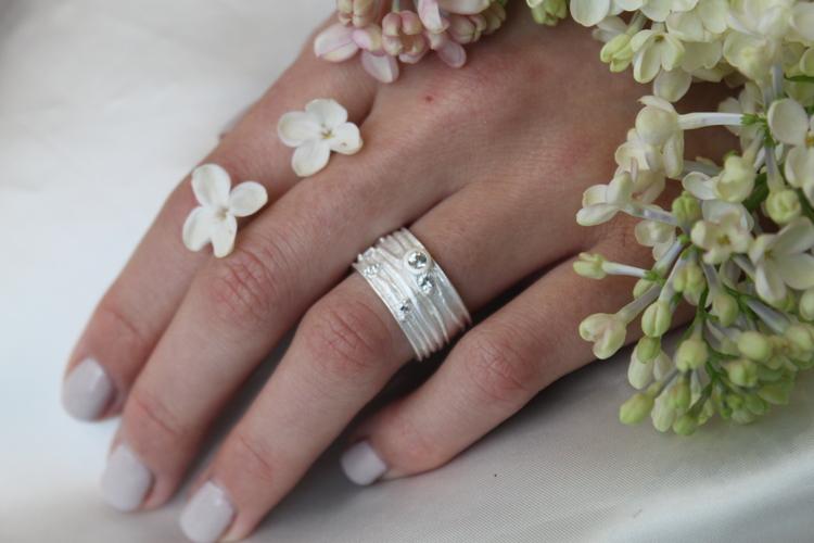 Denna ring består av en större ståtlig diamant och flera ljuvliga små, på ett brett band med en matt grov struktur.
