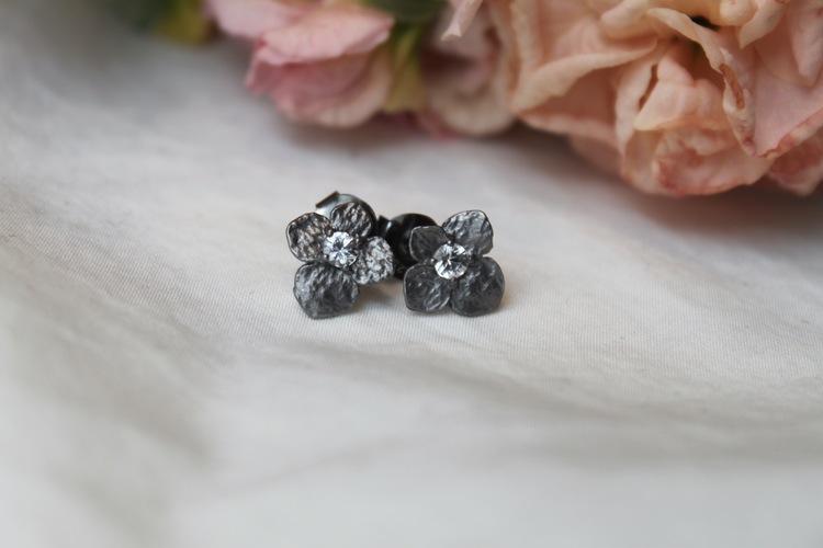 Hydrangea Petite Earrings från Lotta Jewellery är ett par fantastiska örhängen gjorda i matt mörk brons och med vita safirer.