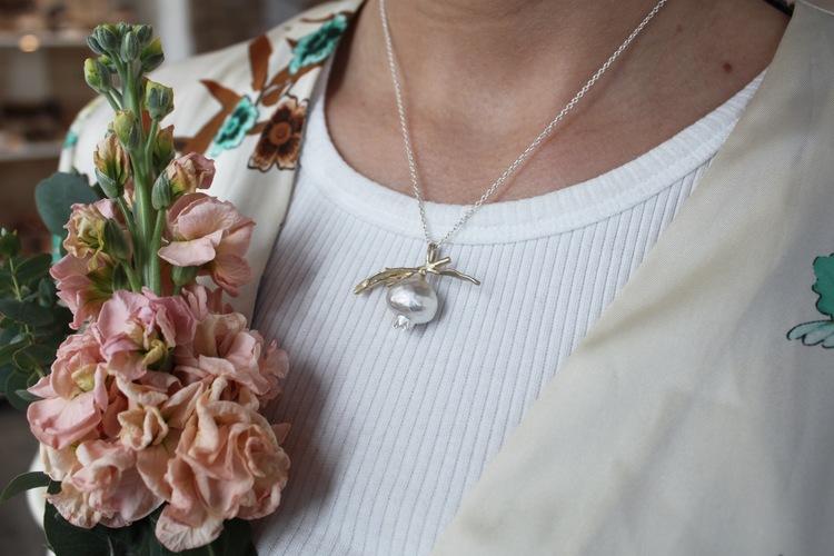 Queen of the pomegranate-halsbandet består av ett ljuvligt granatäpple tillsammans med dess gren och vackra löv. Frukten I sig är gjord i matt silver, medan gren och löv är doppade i 14 k matt guld.
