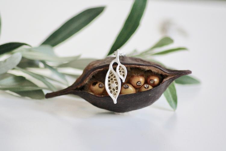 Ett  silverhalsband på kedja med naturliga ihåligheter och frökapselns frukter. Smycket är format i vax och avgjutet från naturens skönhet.